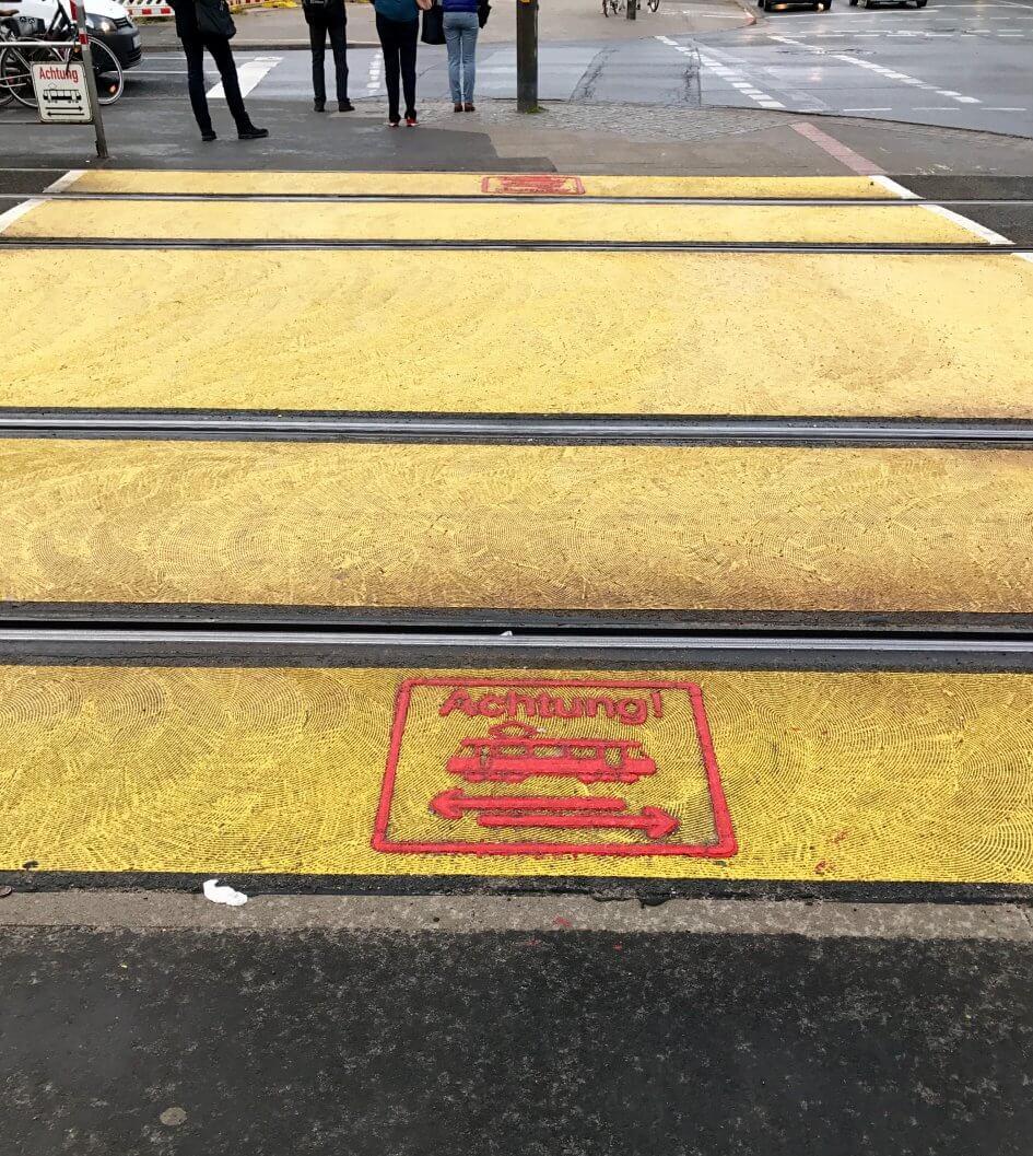 Gelbe Warnmarkierung am Stadtbahnübergang Wallensteinstr. mit Stadtbahnpiktogramm