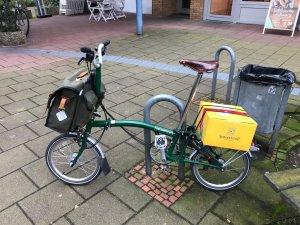 Dunkelgrünes Brompton-Faltrad, das vorn mit einer Fahrradtasche beladen ist und an dem ein Paket auf dem Gepäckträger befestigt ist.