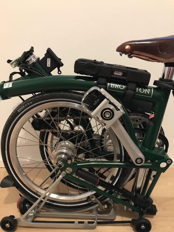 Dunkelgrünes Brompton-Faltrad in zusammengefaltetem Zustand